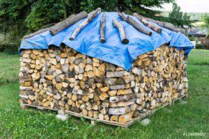 Blaue Holzabdeckplane mit Holzblöcken als Befestigung